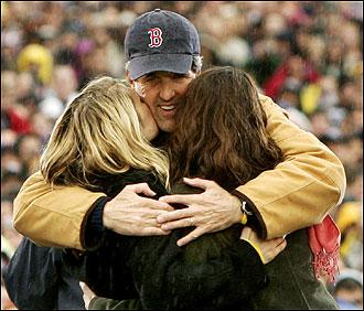 John Kerry, wearing a Red Sox baseball cap, hugs his daughters - AP